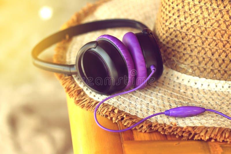 Auriculares púrpuras que mienten en el sombrero de paja imagen de archivo