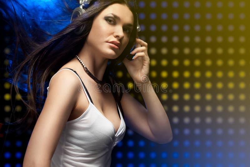 Auriculares que desgastan de DJ de la mujer hermosa imagen de archivo