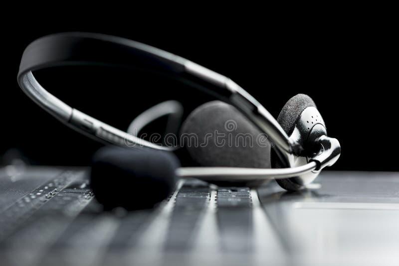 Auriculares que encontram-se em um keyboardHeadset do laptop que encontra-se em um la imagens de stock