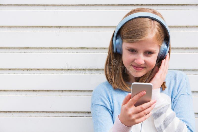 Auriculares que llevan de la muchacha pre adolescente y el escuchar la música en urbano imagen de archivo