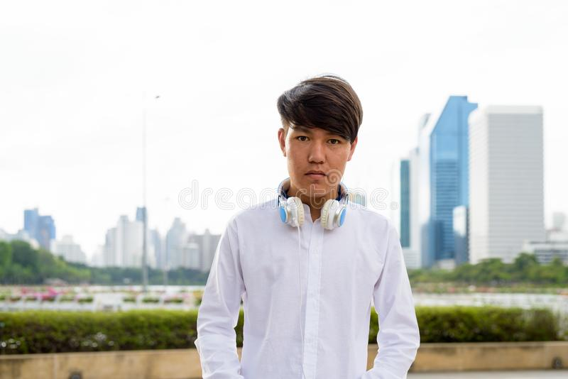 Auriculares que llevan del adolescente asiático joven mientras que se relaja en fotos de archivo