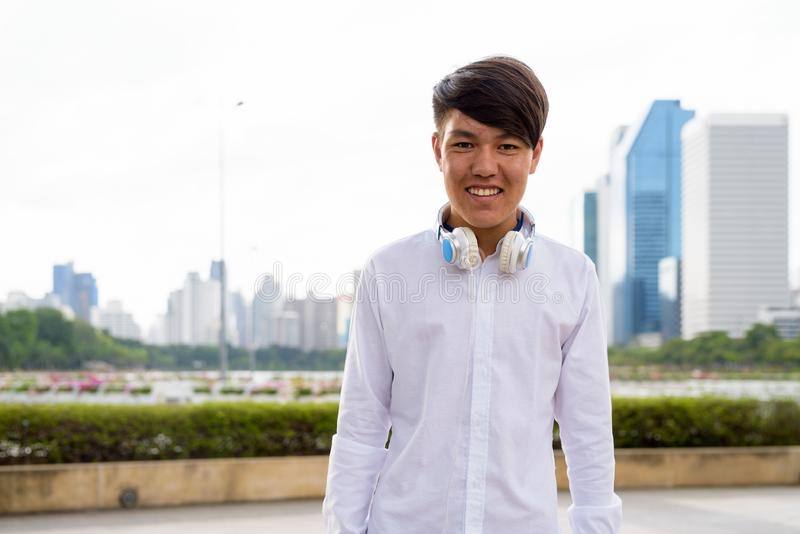 Auriculares que llevan del adolescente asiático joven mientras que se relaja en imagenes de archivo