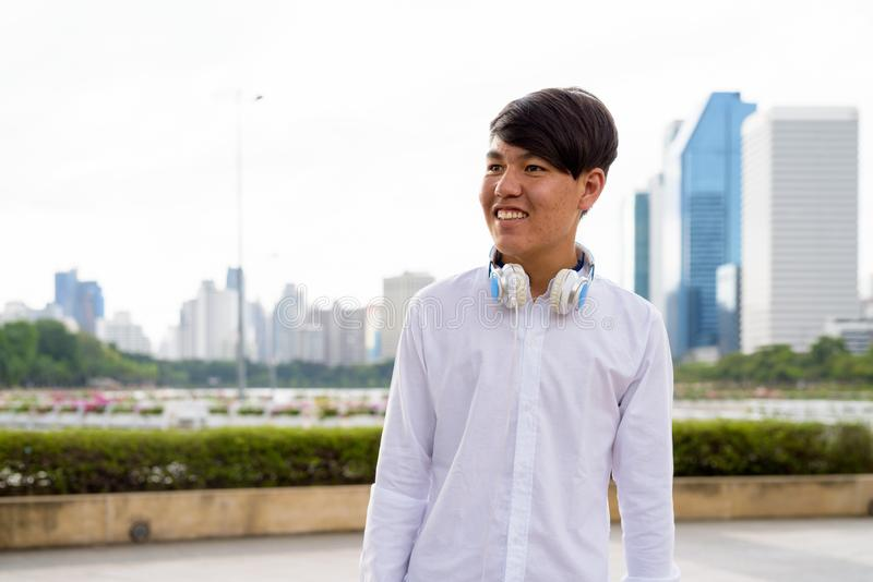 Auriculares que llevan del adolescente asiático joven mientras que se relaja en foto de archivo libre de regalías