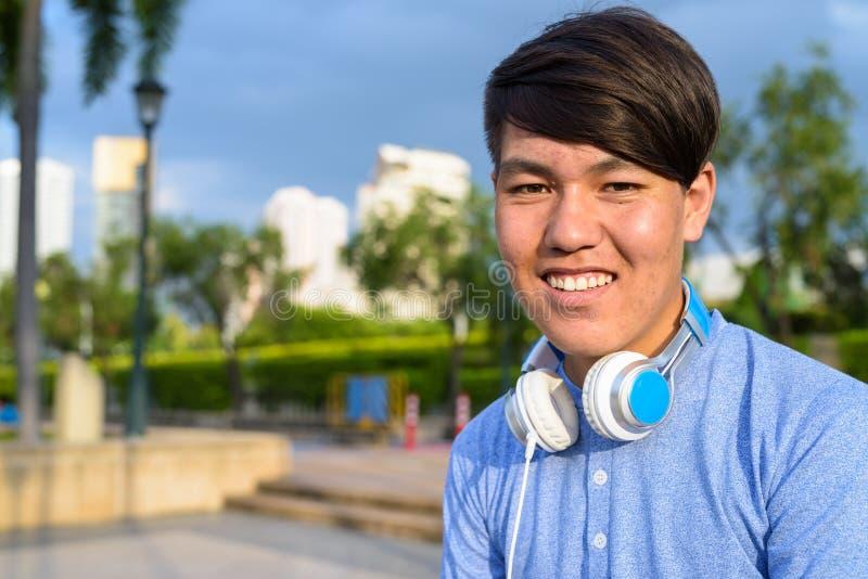 Auriculares que llevan del adolescente asiático joven mientras que se relaja en imagen de archivo
