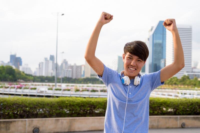 Auriculares que llevan del adolescente asiático joven mientras que se relaja en fotografía de archivo libre de regalías