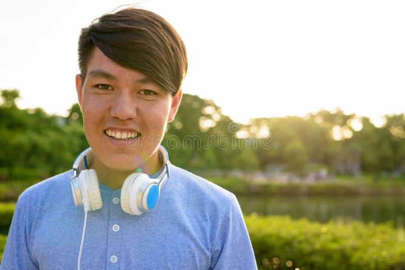 Auriculares que llevan del adolescente asiático joven mientras que se relaja en imagen de archivo libre de regalías