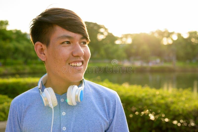 Auriculares que llevan del adolescente asiático joven mientras que se relaja en fotos de archivo libres de regalías