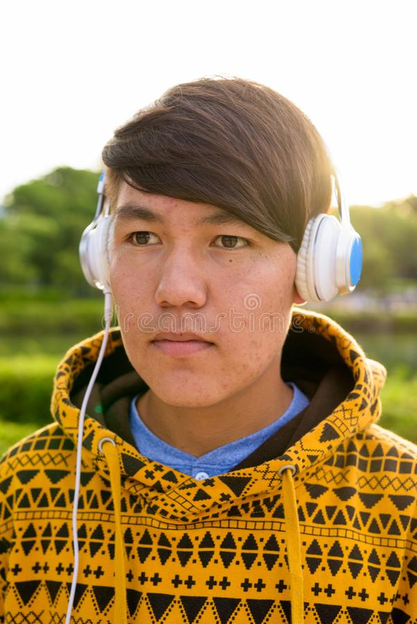 Auriculares que llevan del adolescente asiático joven mientras que se relaja en imágenes de archivo libres de regalías