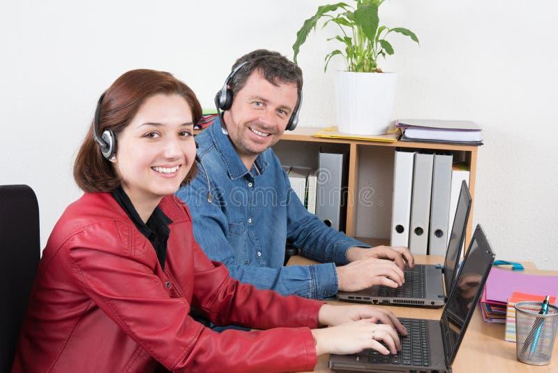 Auriculares que llevan del agente femenino y masculino del servicio de atención al cliente con los colegas que trabajan en fondo  imagenes de archivo