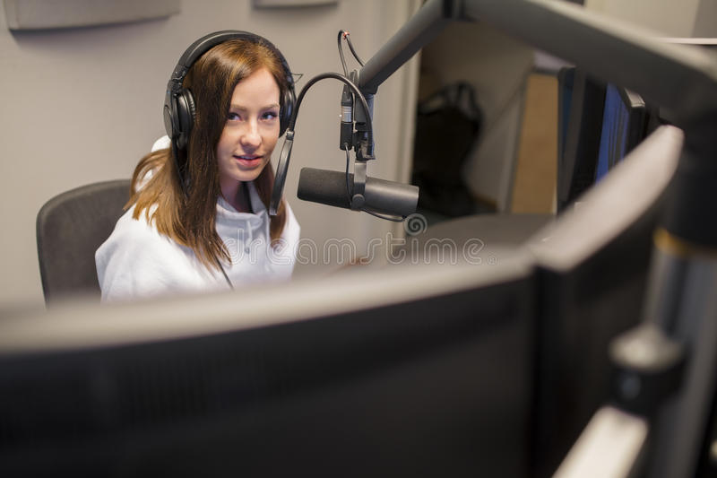 Auriculares que llevan del anfitrión mientras que usa el micrófono en el estudio de radio foto de archivo libre de regalías