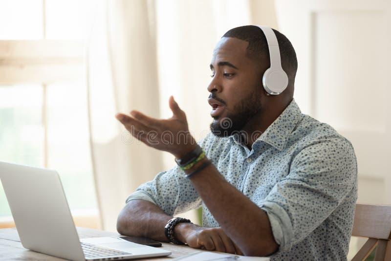 Auriculares que llevan del varón del profesor africano de Skype que hablan mirando el ordenador portátil foto de archivo libre de regalías