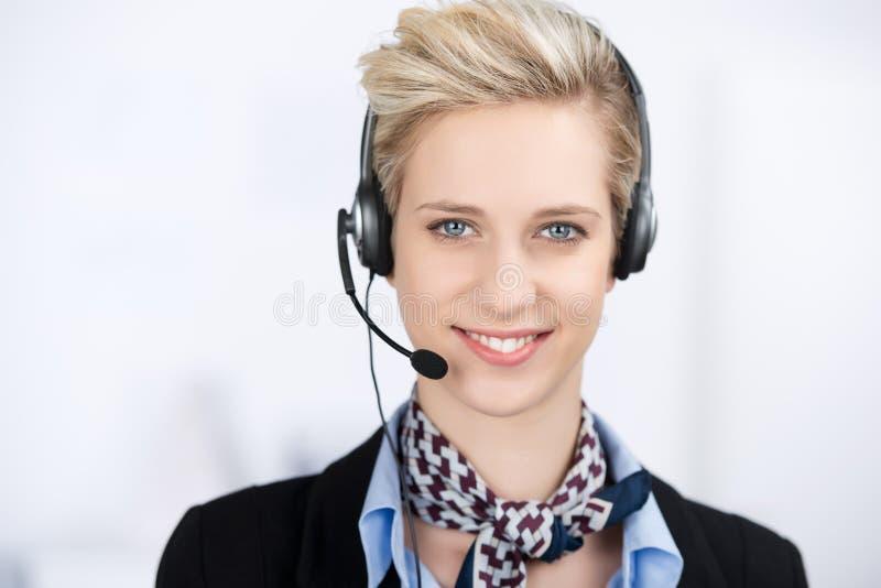 Auriculares que llevan ejecutivas del servicio de atención al cliente femenino imagenes de archivo