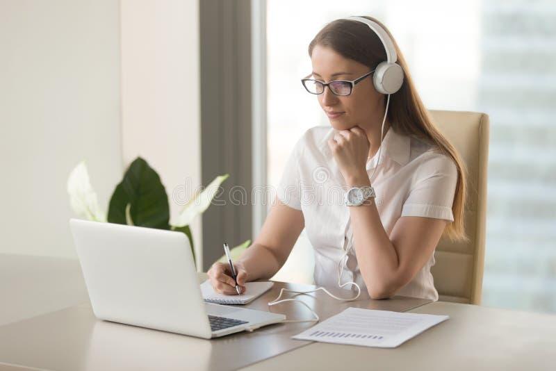 Auriculares que llevan enfocados de la mujer atenta usando el ordenador portátil en offic imagen de archivo libre de regalías