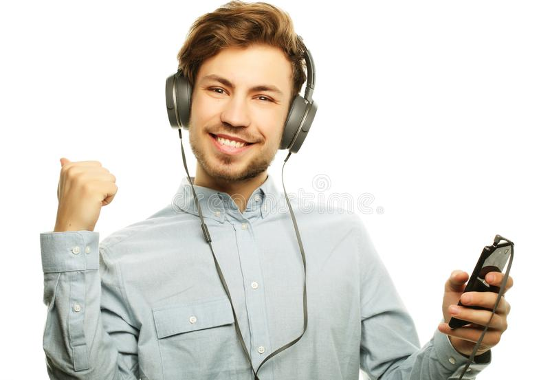 Auriculares que llevan hermosos del hombre joven y el escuchar la música foto de archivo libre de regalías