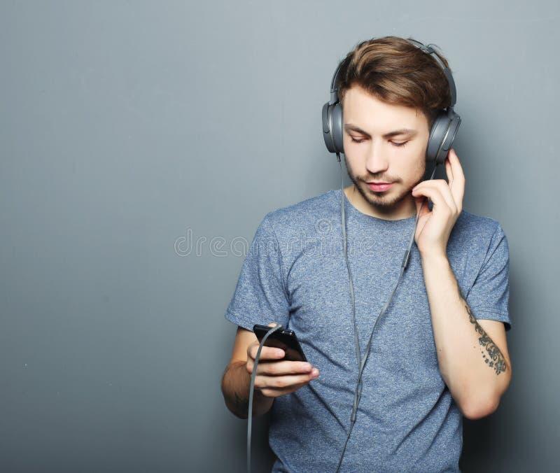 Auriculares que llevan hermosos del hombre joven y sostener el teléfono móvil mientras que se opone a la pared gris foto de archivo