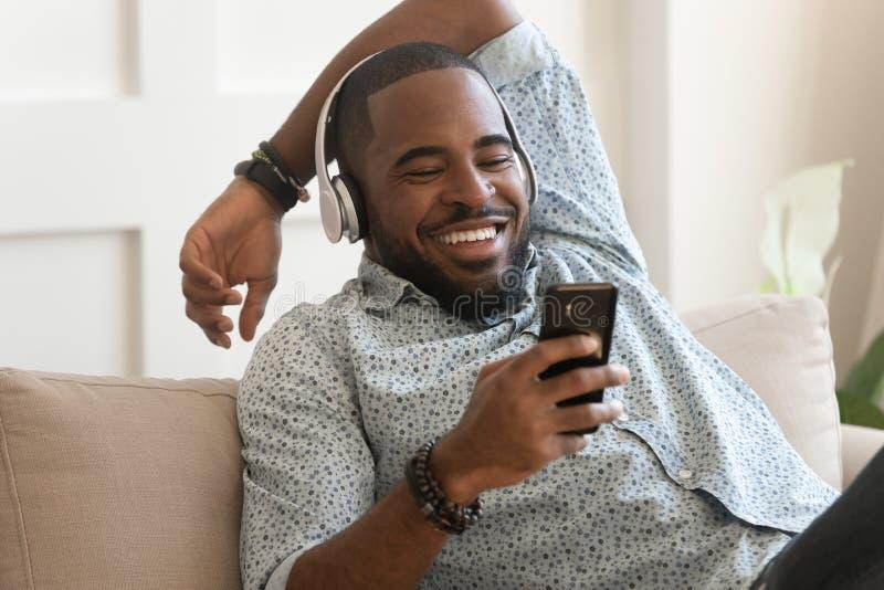 Auriculares que llevan sonrientes del hombre africano joven escuchar la música móvil fotografía de archivo libre de regalías