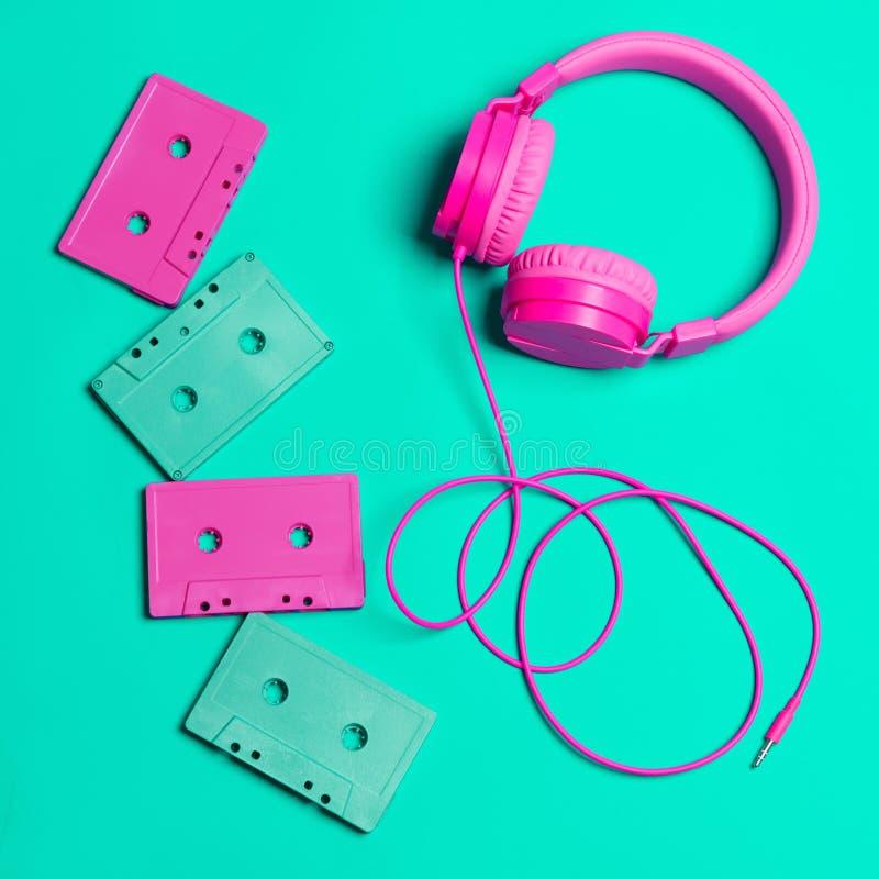 Auriculares rosados y casetes audios con Cdes imagen de archivo