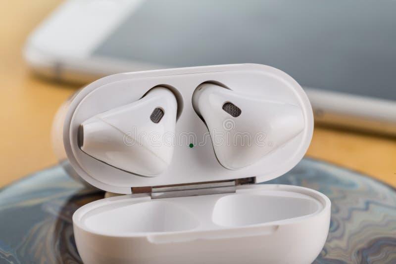 Auriculares sem fio modernos para escutar a música de seu smartphone fotos de stock royalty free