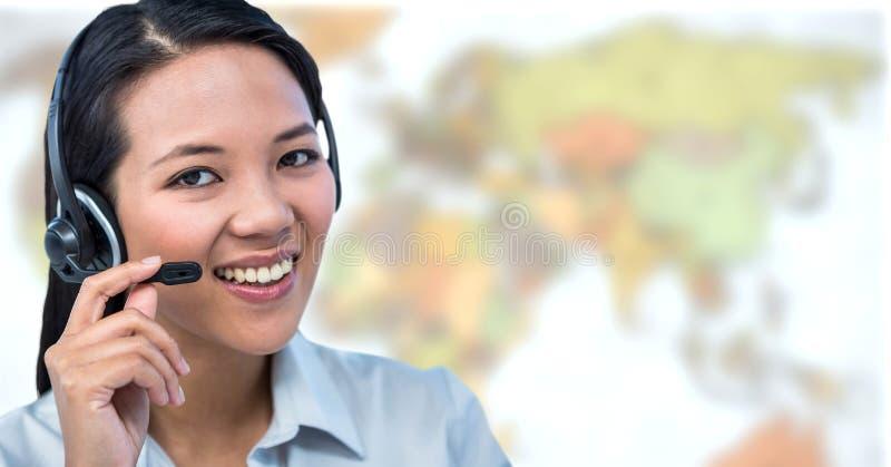 Auriculares vestindo da mulher do agente de viagens na frente do mapa do mundo fotos de stock