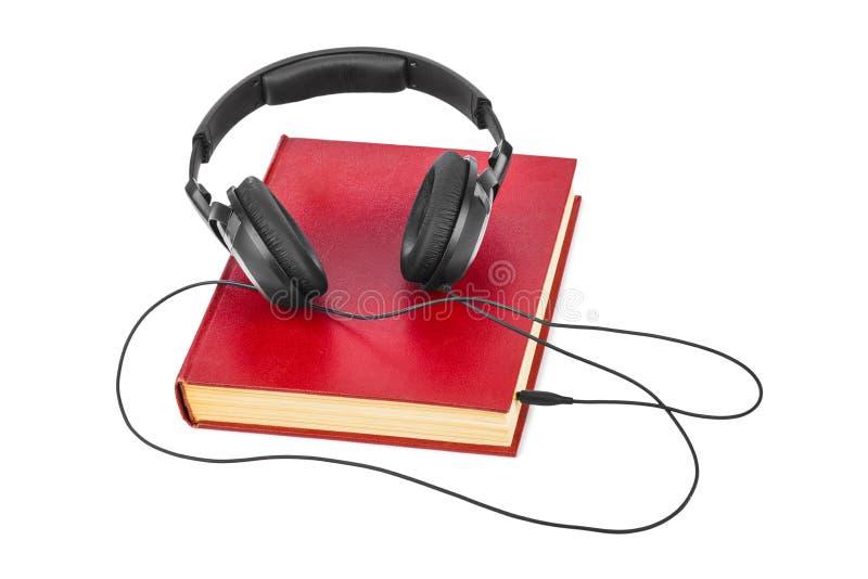 Auriculares y libro fotografía de archivo libre de regalías