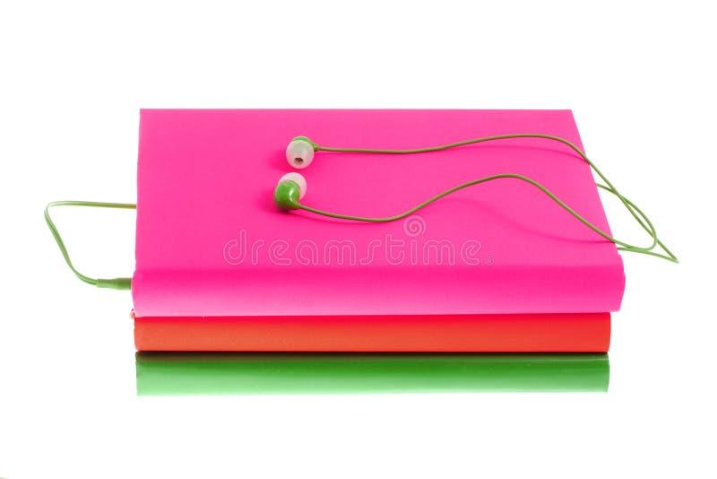 Auriculares y pila de libros multicolores en un fondo blanco imágenes de archivo libres de regalías