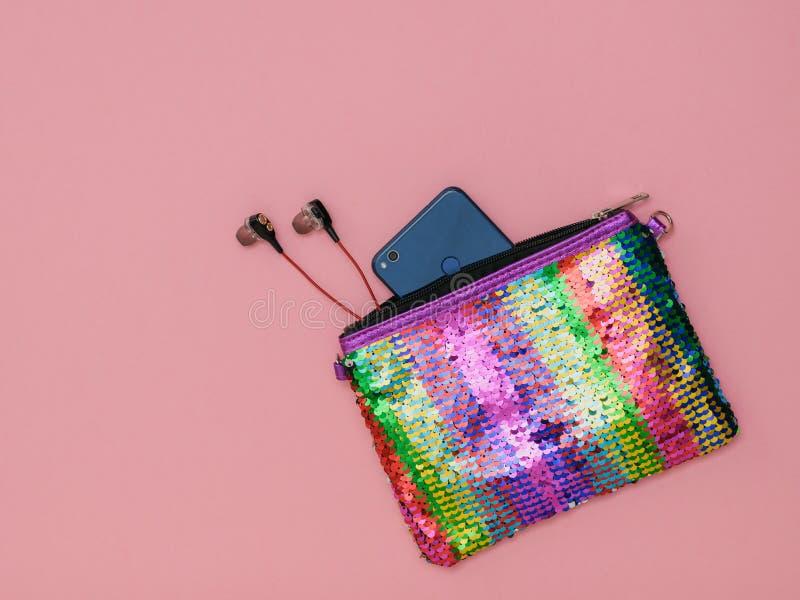 Auriculares y smartphone en un bolso coloreado arco iris en un fondo amarillo Complementos para las mujeres accesorio Endecha pla imagen de archivo