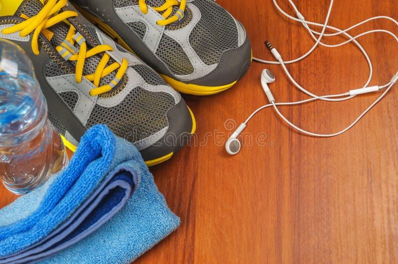Auriculares, zapatos del deporte y toalla foto de archivo libre de regalías