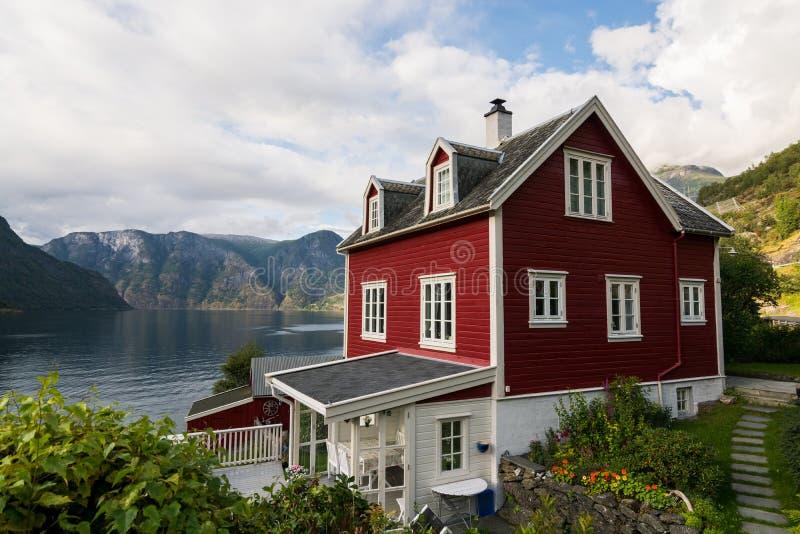 AURLAND, ΝΟΡΒΗΓΙΑ - ΤΟΝ ΑΎΓΟΥΣΤΟ ΤΟΥ 2017: Κόκκινο ξύλινο σπίτι Tradional που στέκεται στην ακτή Aurlandsfjord, Νορβηγία στοκ φωτογραφίες με δικαίωμα ελεύθερης χρήσης