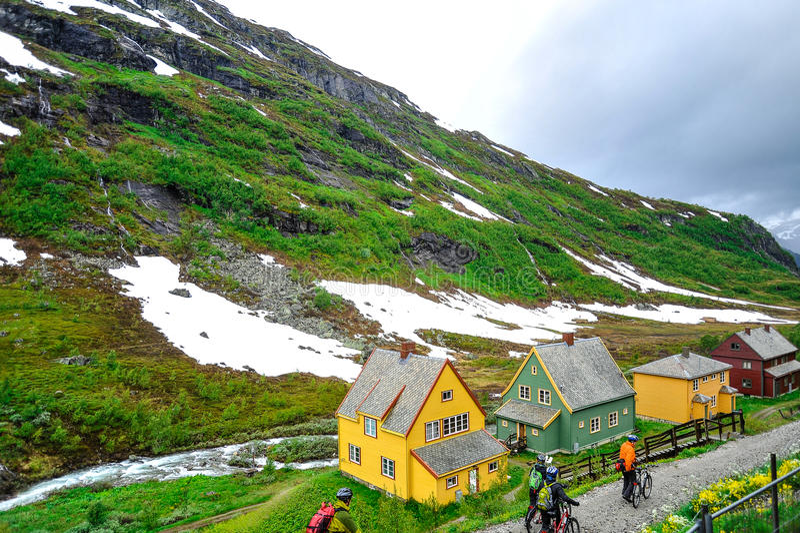 AURLAND, ΝΟΡΒΗΓΙΑ - ΤΟΝ ΙΟΎΛΙΟ ΤΟΥ 2015: Ποδηλάτες που περπατούν τα ποδήλατά τους μέσω μιας μικρής παρόδου δίπλα στο όμορφο πράσι στοκ εικόνες