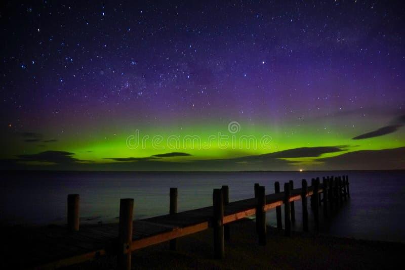 Aurora Australis show by the wharf. Urora Australis show by the wharf. Great green blue purple display of aurora with beams royalty free stock photos