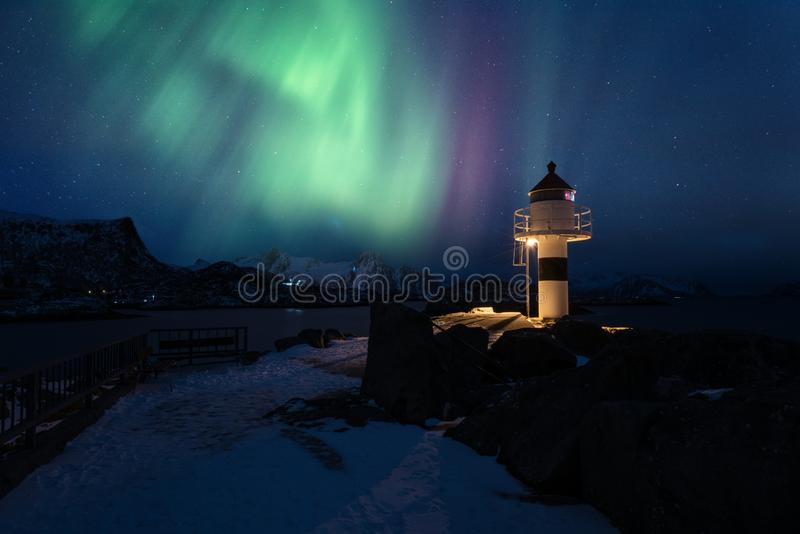 Aurora boreal, aurora borealis em ilhas de Lofoten, Noruega Paisagem do inverno da noite com luzes polares e farol imagem de stock