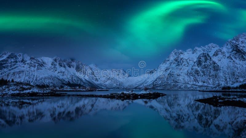 Aurora boreal, aurora borealis, ilhas de Lofoten, Noruega Paisagem do inverno da noite com luzes polares, o céu estrelado e as mo fotos de stock