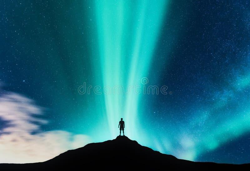 Aurora boreal e silhueta do homem ereto na montanha fotos de stock