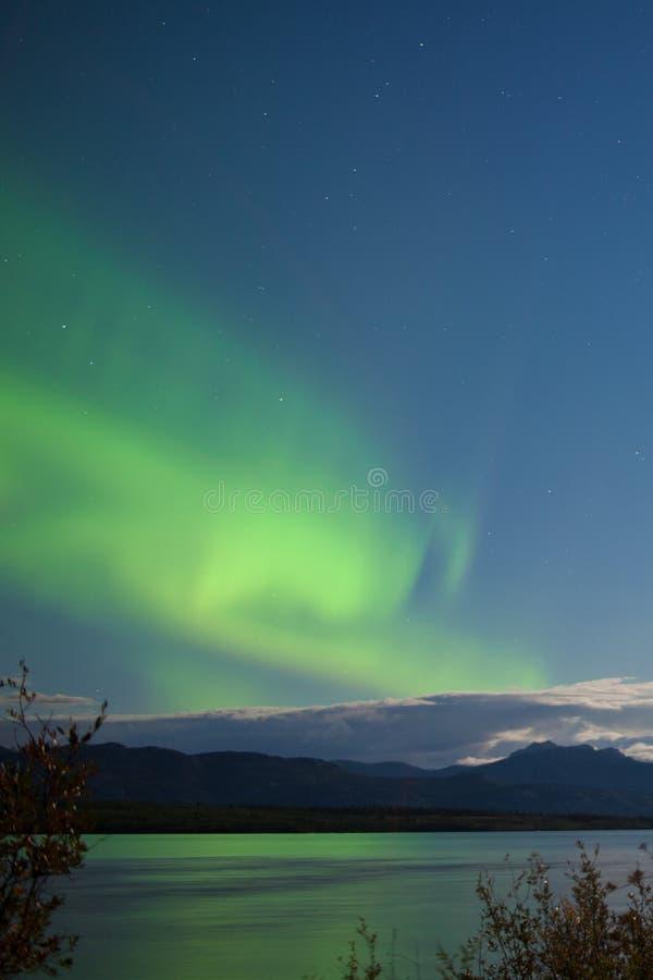 aurora boreal Lua-iluminada das nuvens sobre o lago Laberge imagem de stock