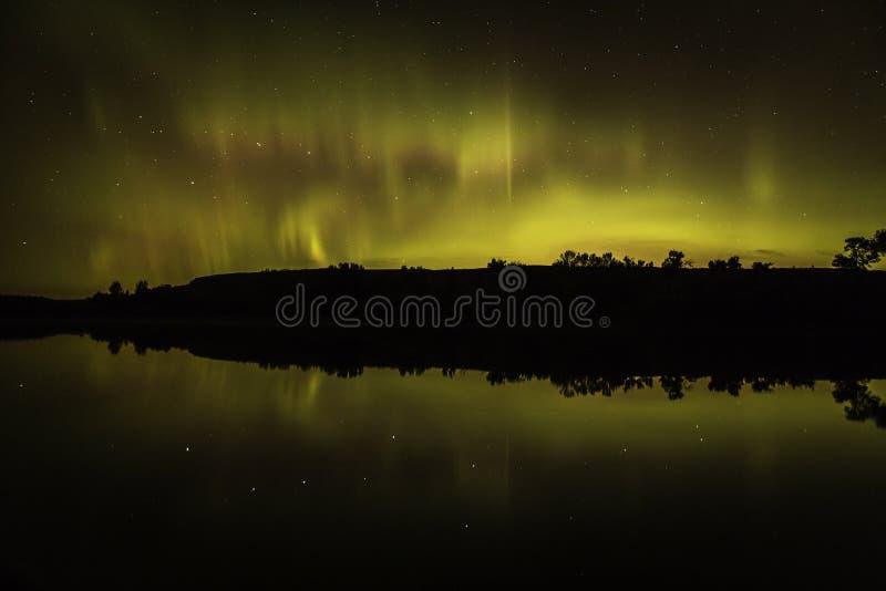 Aurora boreal na noite com uma reflexão imagens de stock