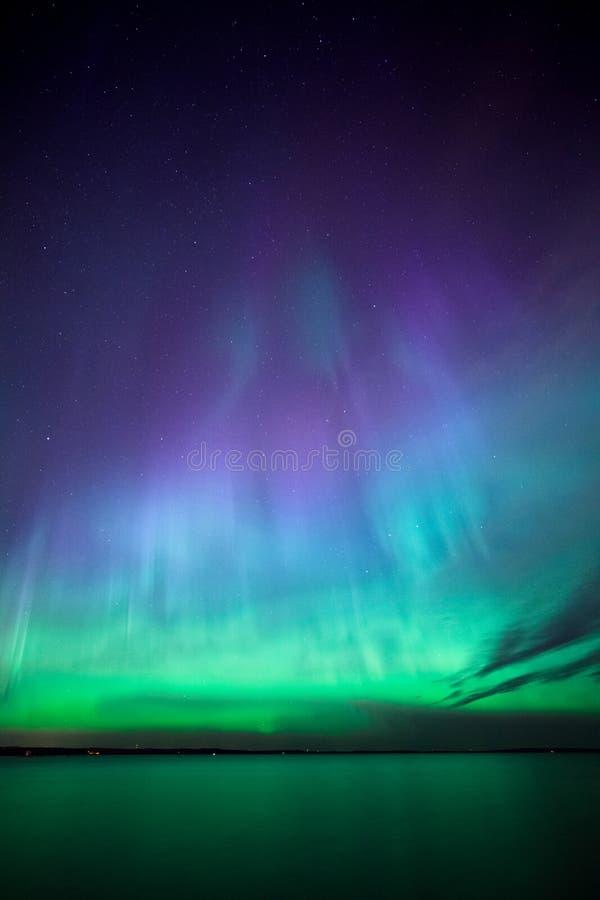 Aurora boreal sobre el lago en Finlandia imagenes de archivo