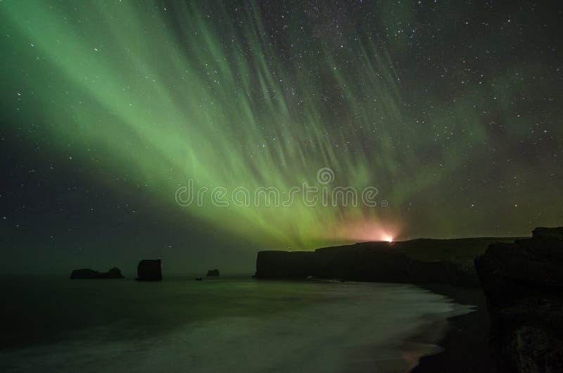 A aurora boreal sobre Reynisfjara encalha com o farol do laey do ³ de Dyrhà que brilha fotografia de stock