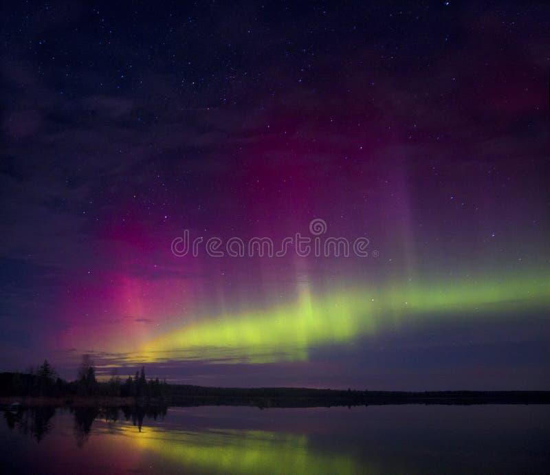 Aurora boreal sobre un lago en Minnesota durante verano imagen de archivo