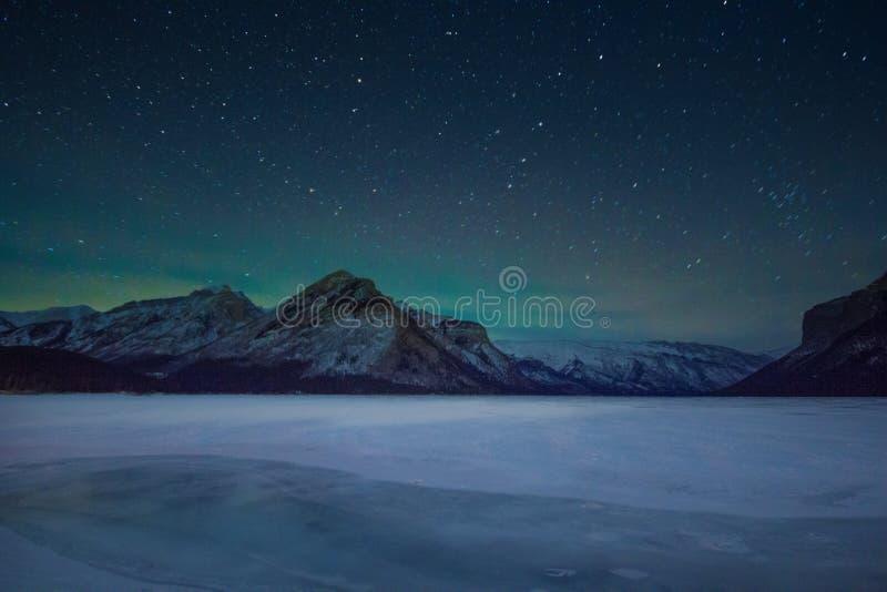 Aurora boreale - aurora borealis e cielo in pieno delle stelle sopra le montagne e il minewanka del lago, parco nazionale di Banf fotografia stock libera da diritti