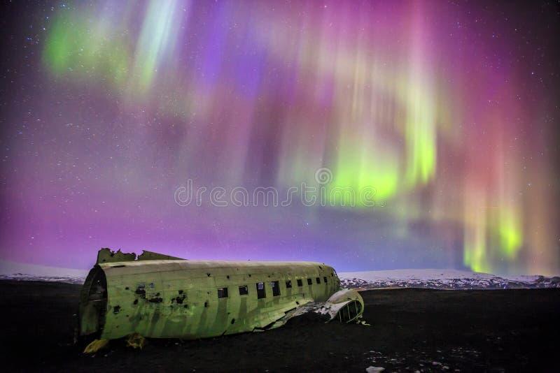 Aurora boreale sopra il relitto piano in Vik, Islanda immagini stock