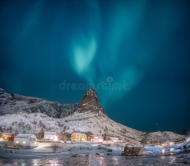 Aurora boreale sulla montagna della neve con il paesino di pescatori alle isole di Lofoten immagine stock