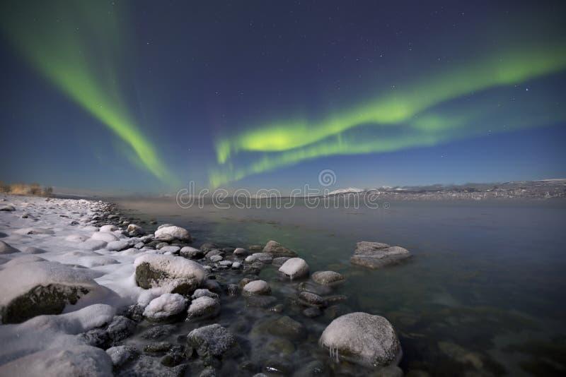 Aurora borealis über einem mondbeschienen Fjord in Nord-Norwegen stockbilder