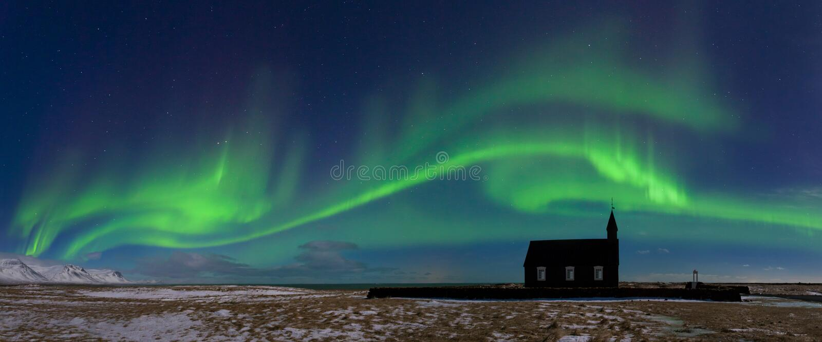 Aurora borealis above the church in Iceland. Green northern lights. Starry sky with polar lights. royalty free stock photography
