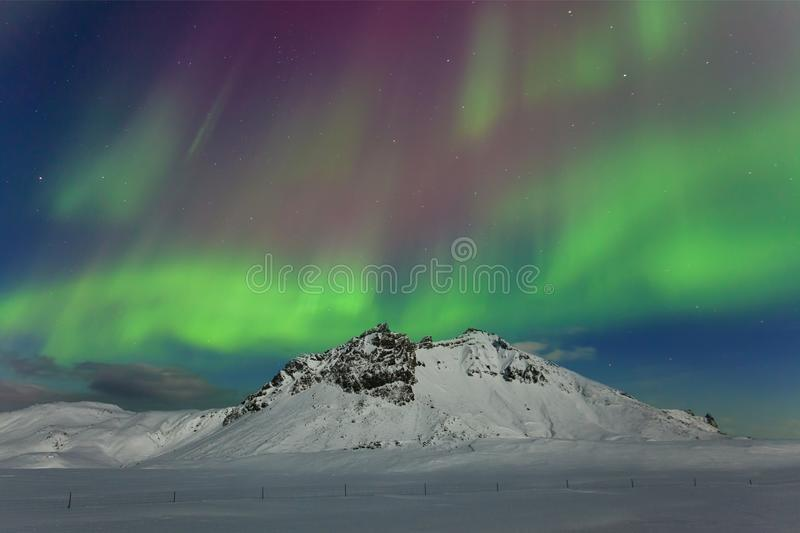 Aurora borealis above the mountains. Reykjavik, Iceland. Green northern lights. Starry sky with polar lights. Night. Winter landscape with aurora stock photos
