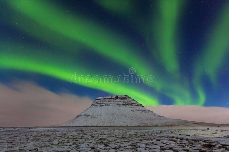 Aurora borealis above the mountains. Reykjavik, Iceland. Green northern lights. Starry sky with polar lights. Night. Winter landscape with aurora royalty free stock photos