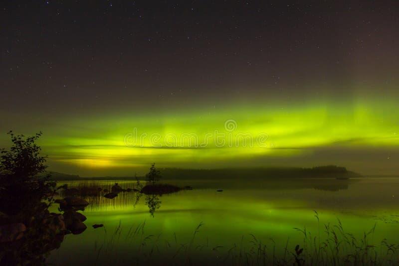 Aurora borealis acima do lago em Finlandia imagens de stock