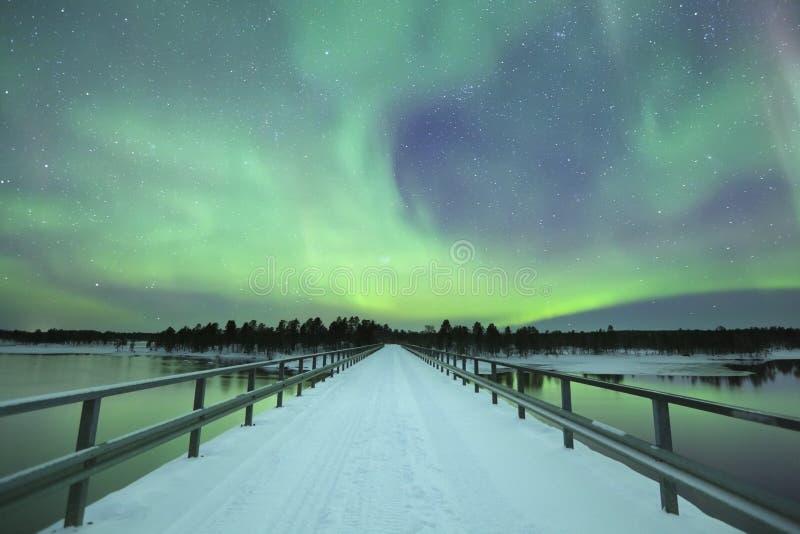 Aurora borealis au-dessus d'un pont en hiver, Laponie finlandaise images stock