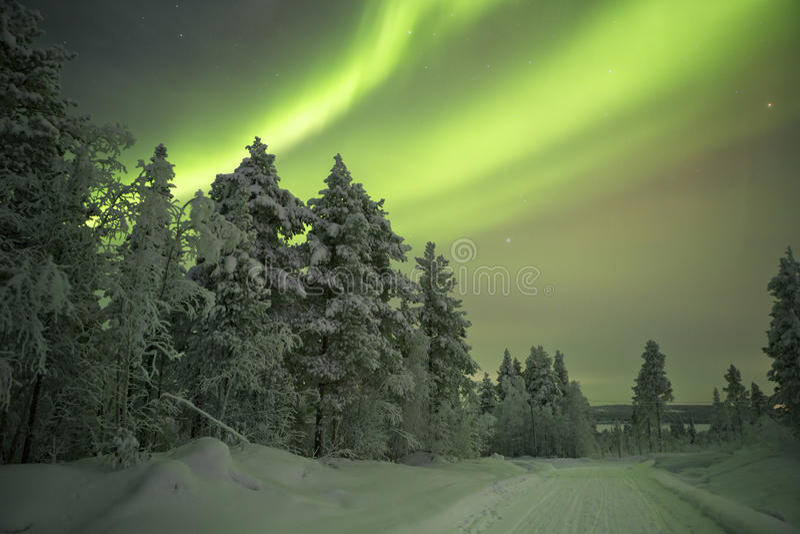 Aurora borealis au-dessus d'une voie par le paysage d'hiver, L finlandais photos stock