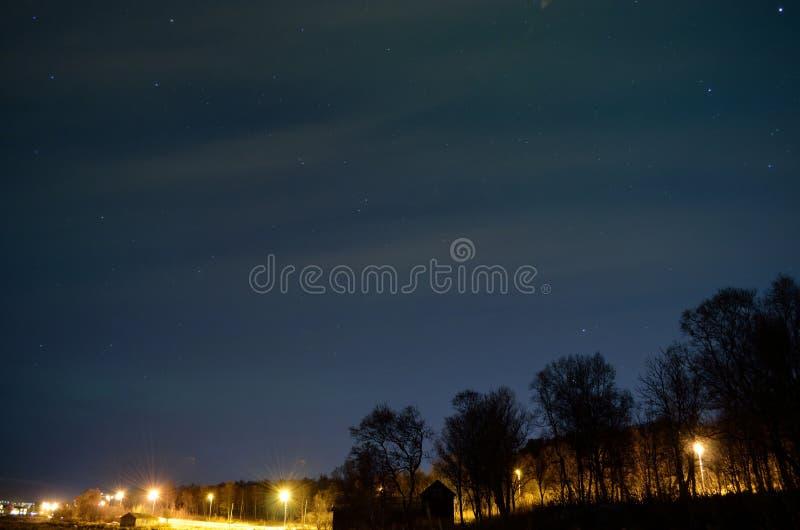 Aurora borealis au-dessus de route, de forêt et de bâtiments publics allumés images libres de droits
