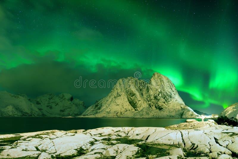 Aurora borealis che ballano sulla montagna in paesino di pescatori a Reine e Sakrisoy, Lofoten, Norvegia che visita le isole di L fotografie stock